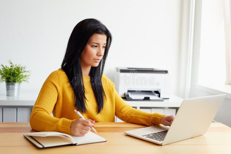 Vrouw die in een bureau met laptop werken royalty-vrije stock foto's