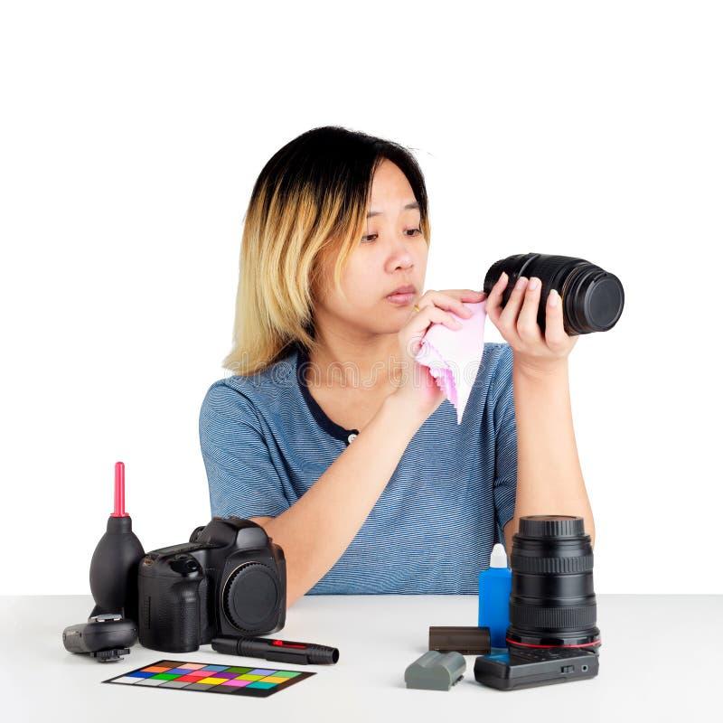 Vrouw die een camera met doek en fotografiemateriaal op lijst schoonmaken stock afbeelding