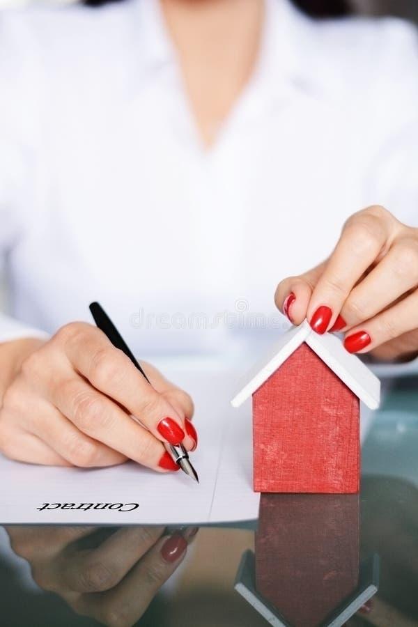 Vrouw die een contract ondertekenen wanneer het kopen van een nieuw huis met hypotheeklening, portretbeeld stock afbeeldingen