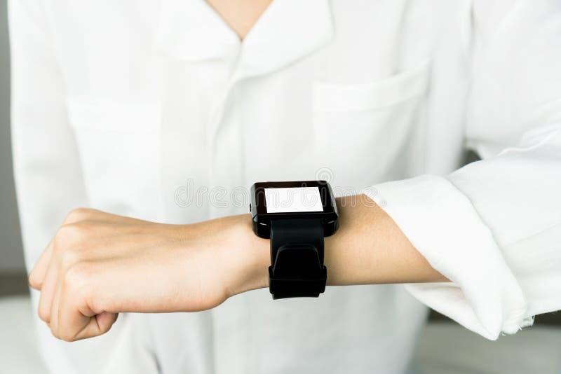 Vrouw die een digitale klok vooraf vertoning en technologiein mededeling gebruiken royalty-vrije stock foto