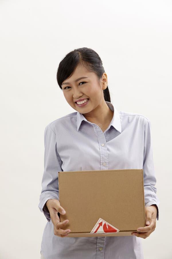 Vrouw die een doos houdt stock afbeeldingen