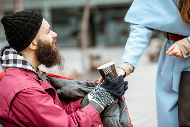 Vrouw die een drank geven aan een dakloze bedelaar royalty-vrije stock foto's