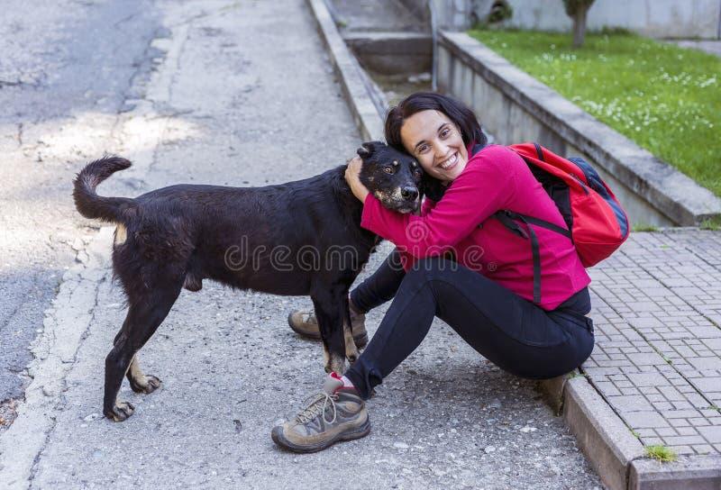 Vrouw die een droevige verdwaalde hond koestert stock foto's