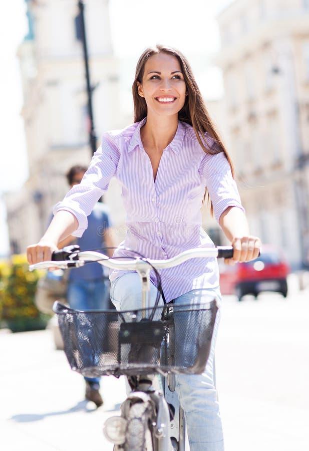 Vrouw die een fiets berijden stock foto