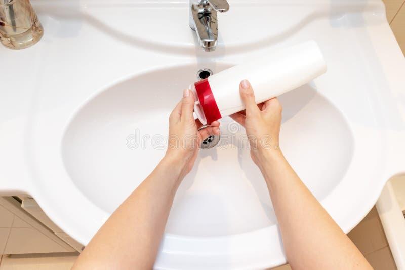 Vrouw die een fles het reinigen oplossing, vloeibare zeep voor washanden openen stock afbeeldingen