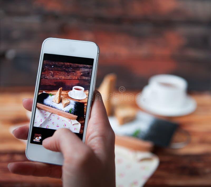 Vrouw die een foto van dessert met smartphone nemen stock afbeeldingen