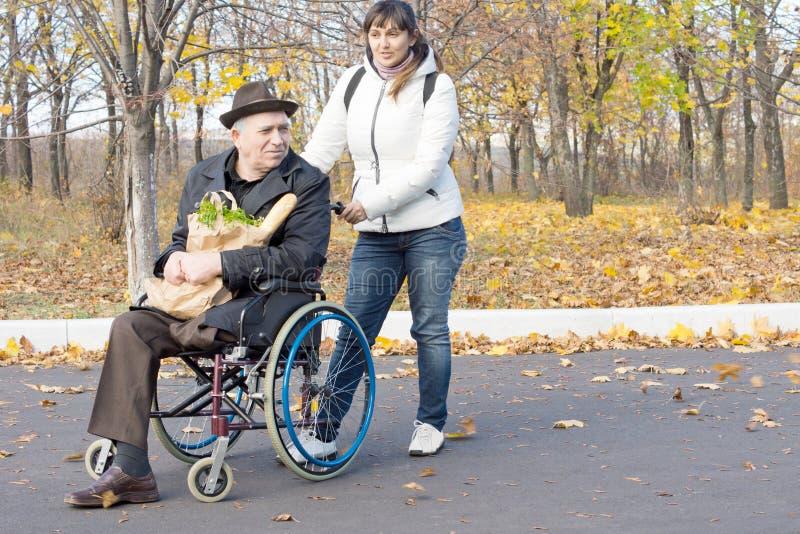 Vrouw die een gehandicapte gepensioneerde in een rolstoel helpen royalty-vrije stock fotografie