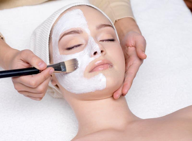 Vrouw die een gezichts kosmetisch masker heeft stock afbeeldingen