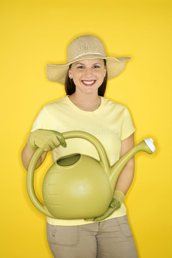 Vrouw die een gieter houdt. royalty-vrije stock afbeeldingen