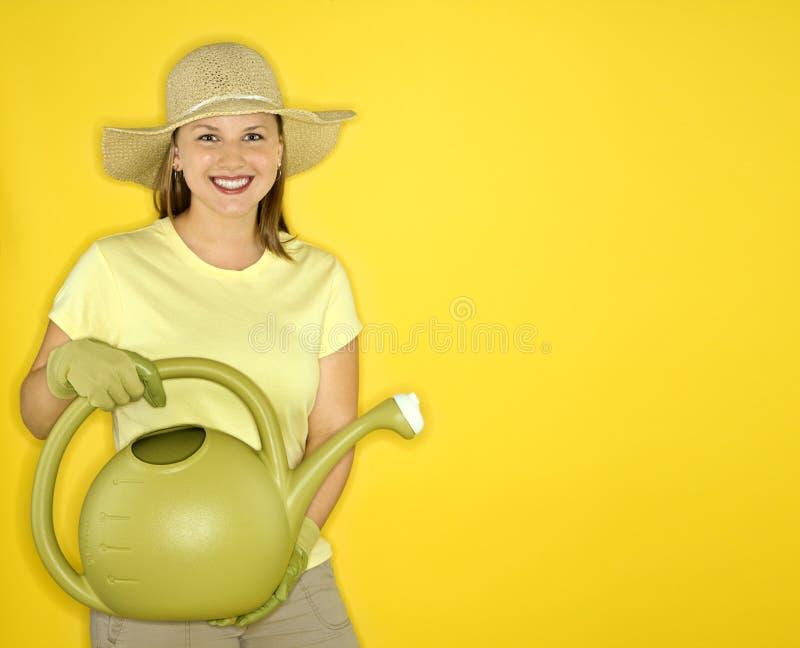 Vrouw die een gieter houdt. stock foto