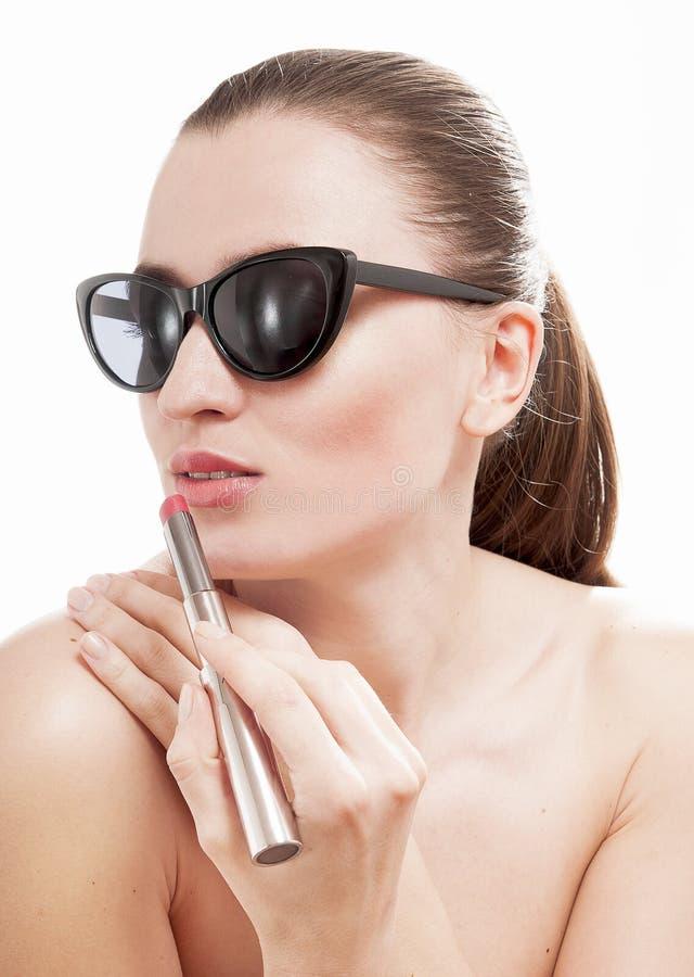 Vrouw die een glamour rode lippenstift op lippen toepassen. royalty-vrije stock afbeeldingen