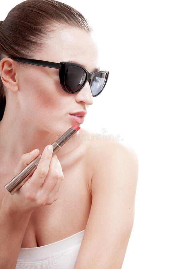 Vrouw die een glamour rode lippenstift op lippen toepassen. royalty-vrije stock fotografie