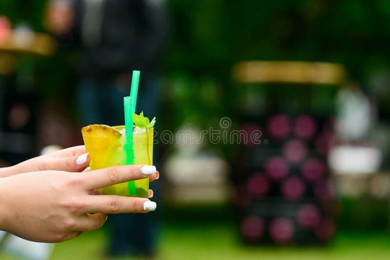 Vrouw die een glas met de zomer verse gele koude uit cocktail houden stock afbeelding