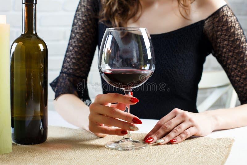 Vrouw die een glas van rood blauw wachten voor de mens houden stock afbeeldingen