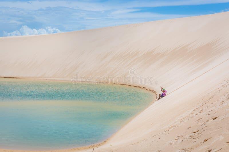 Vrouw die een goede tijd hebben, die een reusachtig zandduin in een verbazend scenario, natuurlijke poollagune op de bodem naar b stock afbeelding