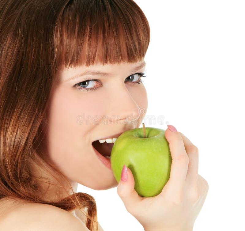 Vrouw die een groene die appel eten over wit wordt ge?soleerd stock foto's