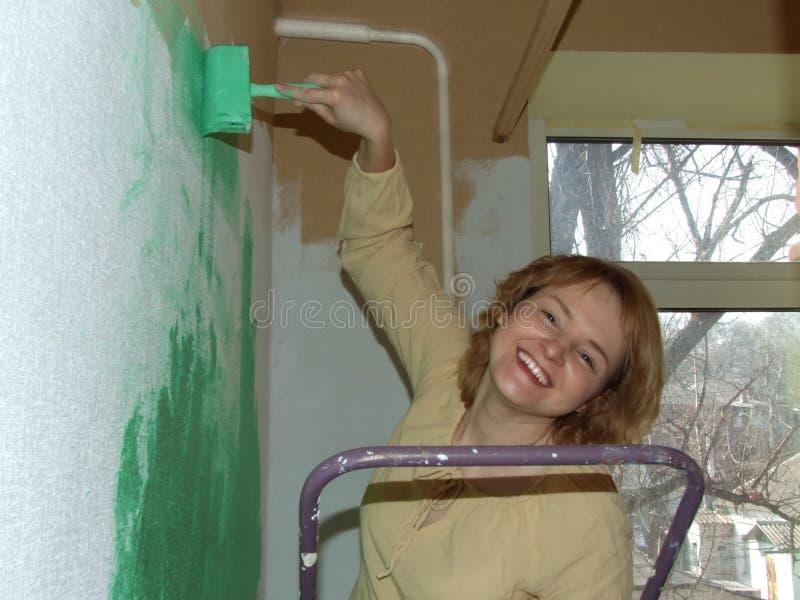 Vrouw die een groene muur schildert royalty-vrije stock foto