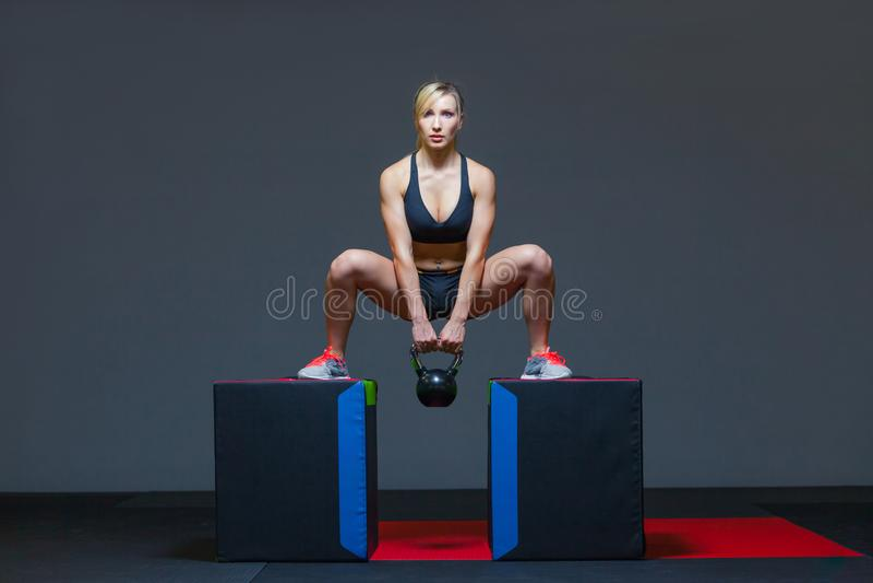 Vrouw die in een gymnastiek met een kettlebellgewicht uitoefenen, op kubussen royalty-vrije stock afbeeldingen