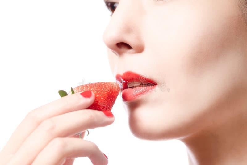 Vrouw die een heerlijke rijpe rode aardbei eten stock fotografie