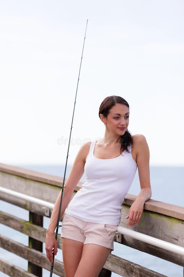 Vrouw die een hengel houden en op een spoor leunen royalty-vrije stock afbeelding