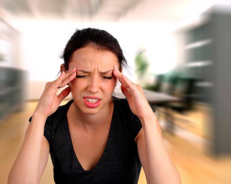 Vrouw die een hoofdpijn hijst stock afbeelding