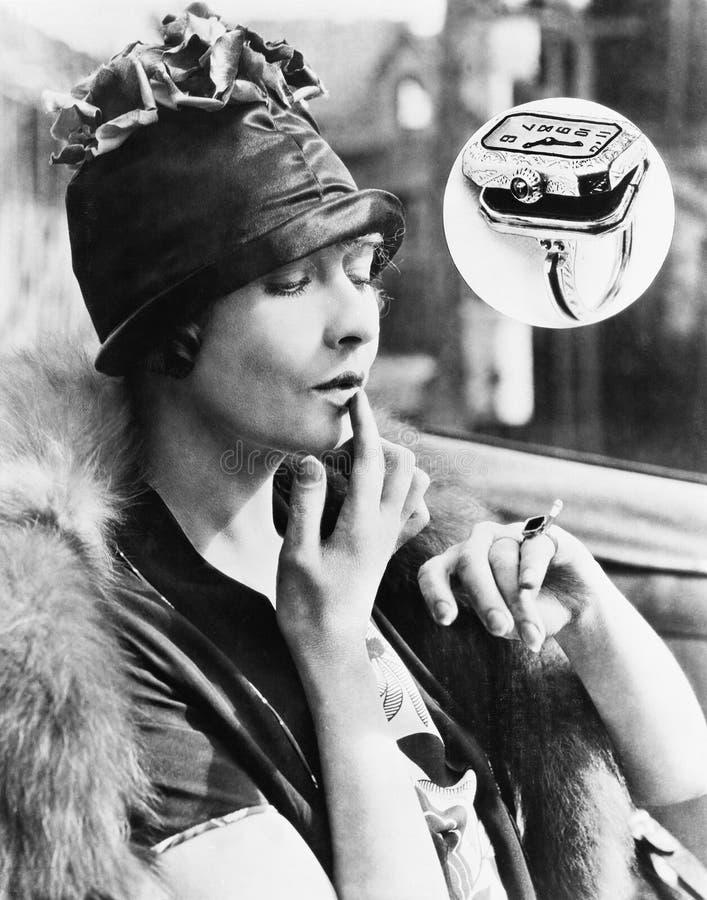 Vrouw die een horlogering bekijken (Alle afgeschilderde personen leven niet langer en geen landgoed bestaat Leveranciersgaranties stock foto