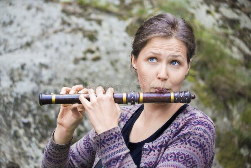 Vrouw die een Indische houten fluit spelen stock afbeeldingen