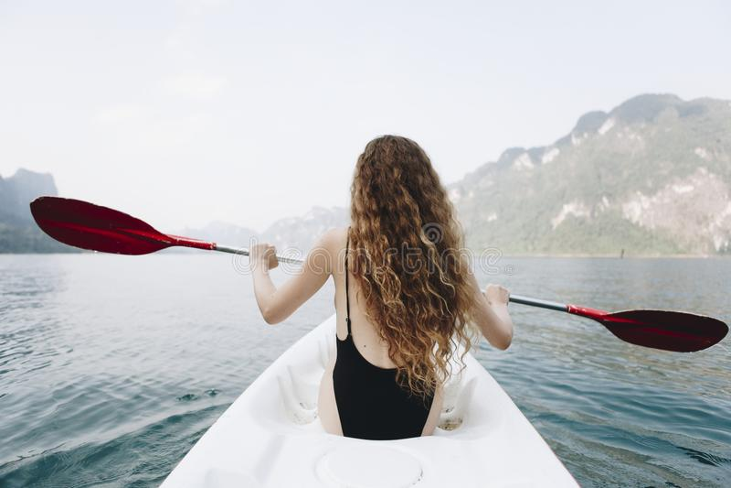 Vrouw die een kano paddelen door een nationaal park royalty-vrije stock fotografie