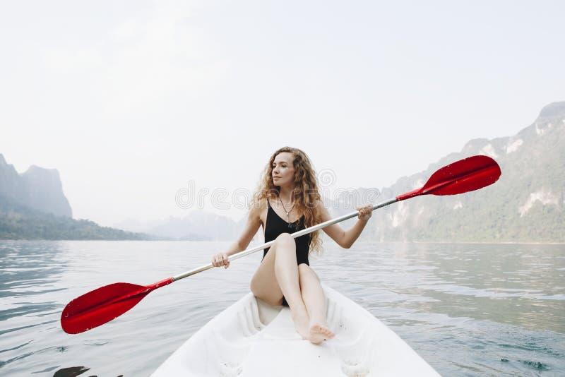 Vrouw die een kano paddelen door een nationaal park stock afbeelding