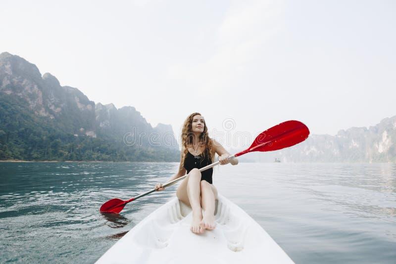 Vrouw die een kano paddelen door een nationaal park stock fotografie