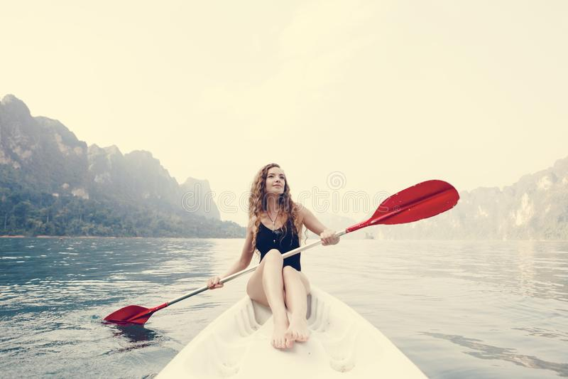 Vrouw die een kano paddelen door een nationaal park stock afbeeldingen