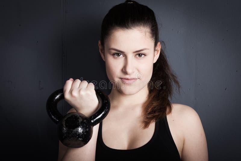 Vrouw die een kettlebell houden en aan camera glimlachen - crossfit fitn stock fotografie