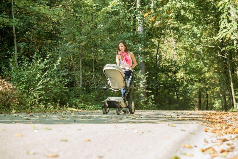 Vrouw die een kinderwagen of een kinderwagen duwen royalty-vrije stock fotografie