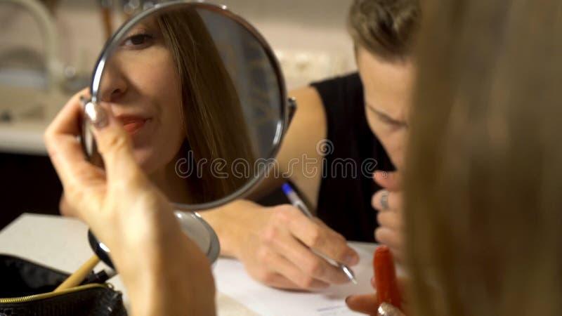 Vrouw die een kleine spiegel in haar hand bekijken terwijl haar vriend die iets schrijven Paarzitting bij een lijst in a royalty-vrije stock afbeelding