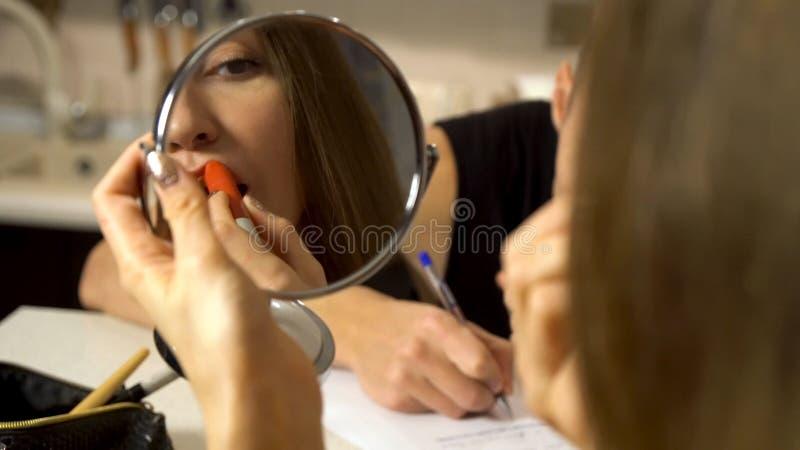 Vrouw die een kleine spiegel in haar hand bekijken terwijl haar vriend die iets schrijven Paarzitting bij een lijst in a stock fotografie