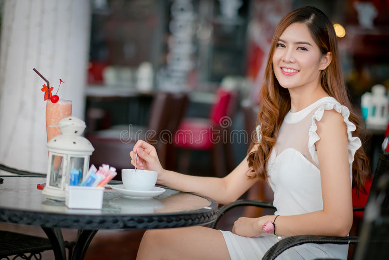 Vrouw die een koffie van een kop in een restaurantterras drinken royalty-vrije stock foto
