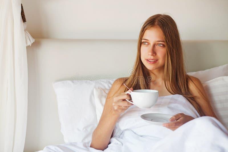 Vrouw die een kop thee in bed hebben stock foto