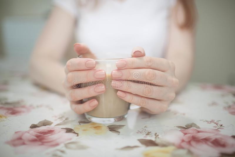 Vrouw die een kop van koffie in haar handen houden stock foto's