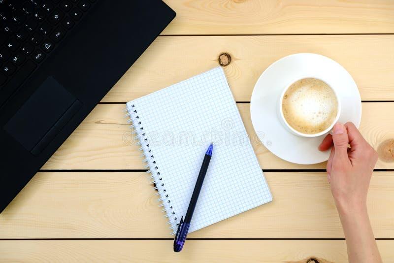 Vrouw die een kop van koffie houdt Lege spatie, pen, laptop stock foto