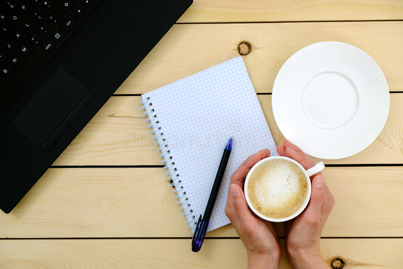 Vrouw die een kop van koffie houdt Lege spatie, pen, laptop stock afbeelding