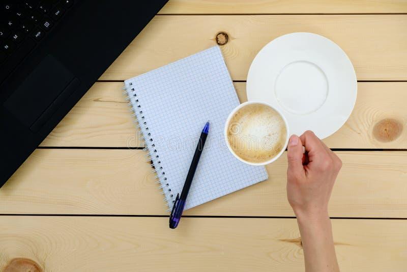 Vrouw die een kop van koffie houdt Lege spatie, pen, laptop royalty-vrije stock afbeelding