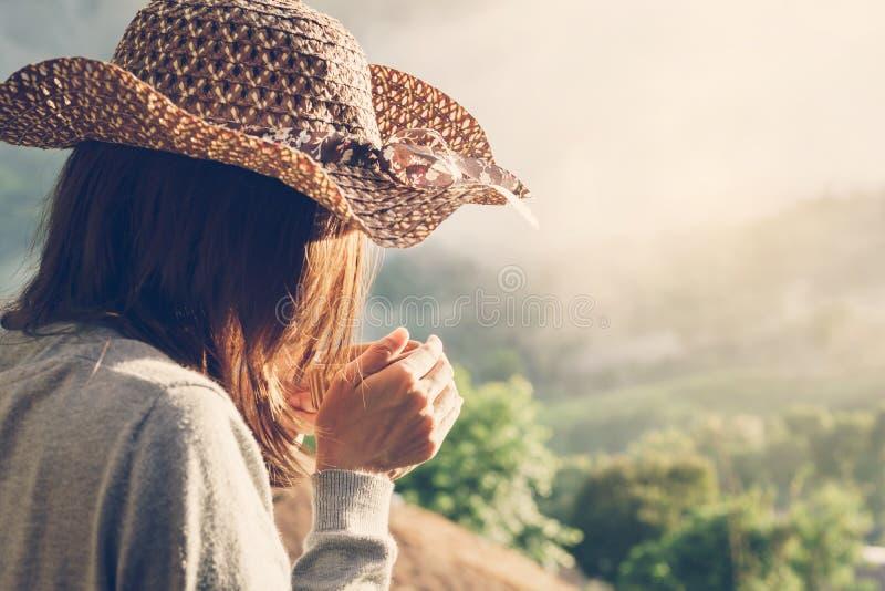Vrouw die een kop van koffie met mooi landschap houden stock foto