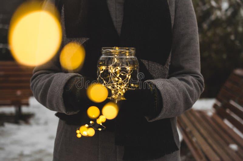 Vrouw die een kruik met Kerstmislichten houden stock afbeeldingen