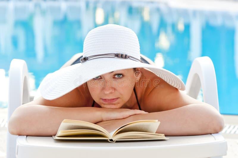 Vrouw die in een ligstoel met een boek liggen en dichtbij de pool zonnebaden royalty-vrije stock foto