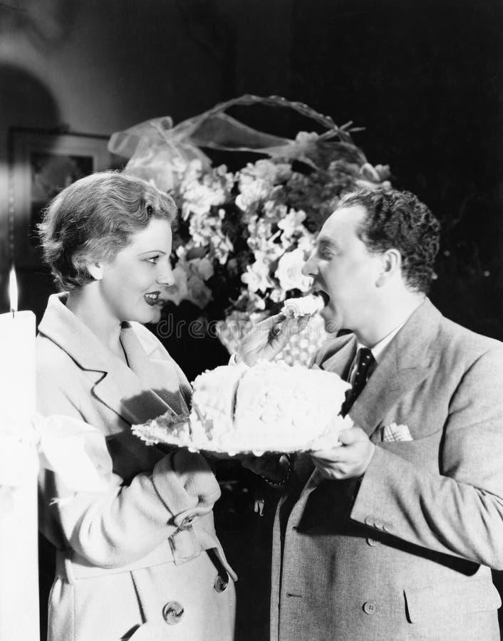 Vrouw die een man een stuk van cake voeden (Alle afgeschilderde personen leven niet langer en geen landgoed bestaat Leveranciersg royalty-vrije stock foto