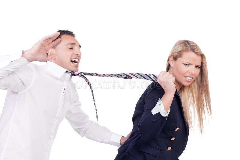 Vrouw die een man trekken door zijn band stock afbeeldingen