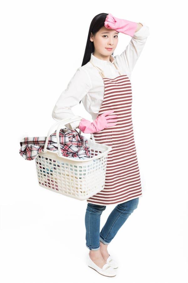 Vrouw die een mand van de huishoudelijk werkholding van wasserij doen royalty-vrije stock foto's