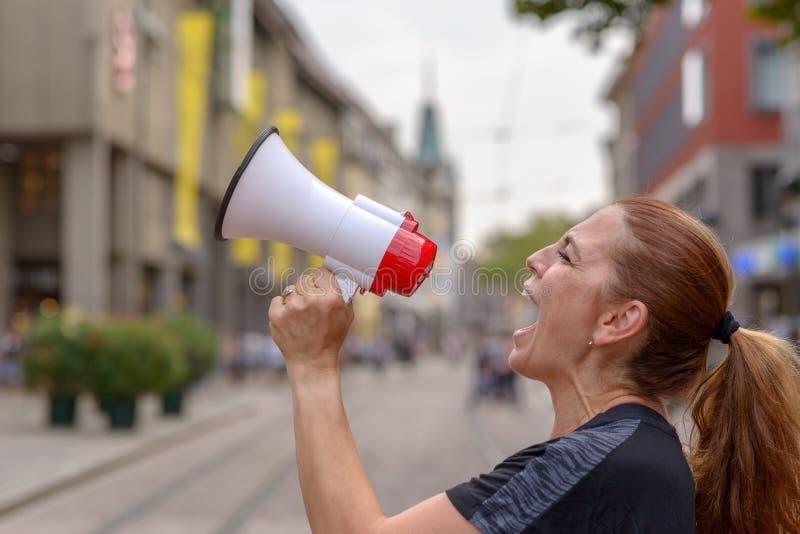 Vrouw die in een megafoon schreeuwt royalty-vrije stock afbeeldingen