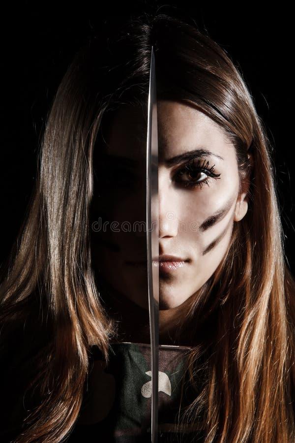 Vrouw die een mes houden bij het midden van haar gezicht royalty-vrije stock foto's