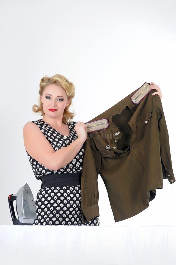 Vrouw die een militaire uniformjas strijken royalty-vrije stock foto's